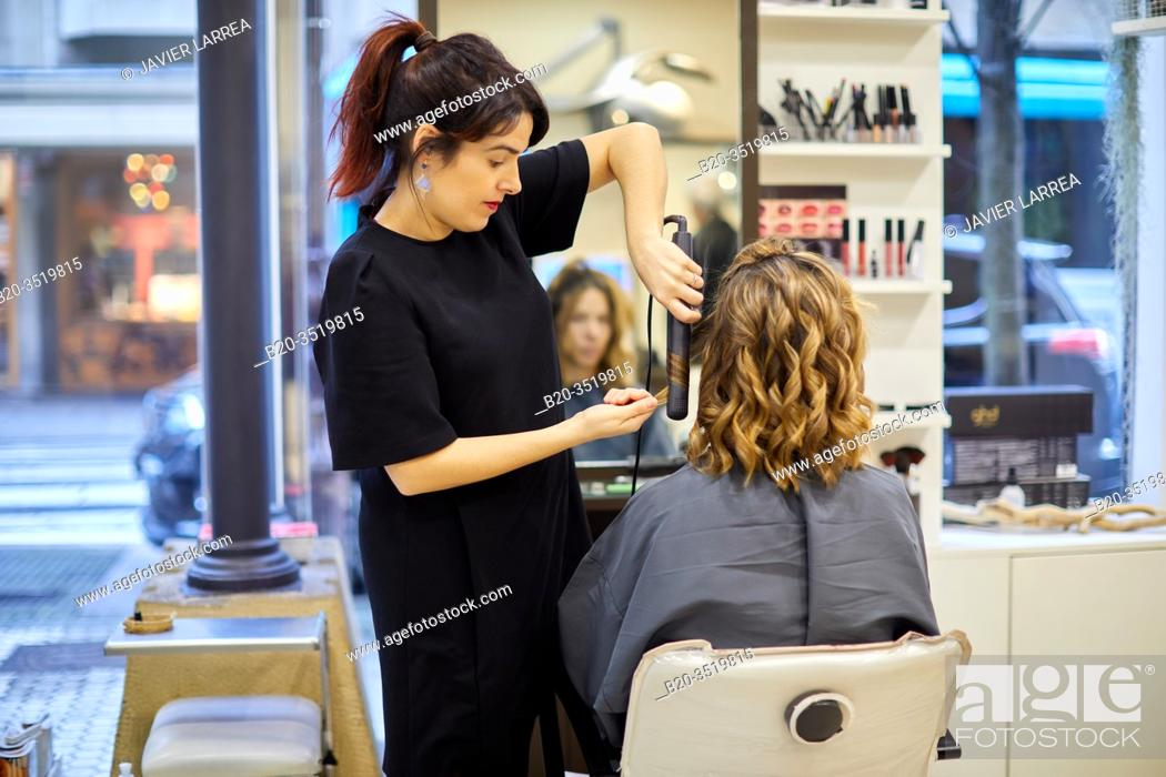 Stock Photo: Hairdresser combing woman, hair straightener, hairdressing salon and beauty clinic.