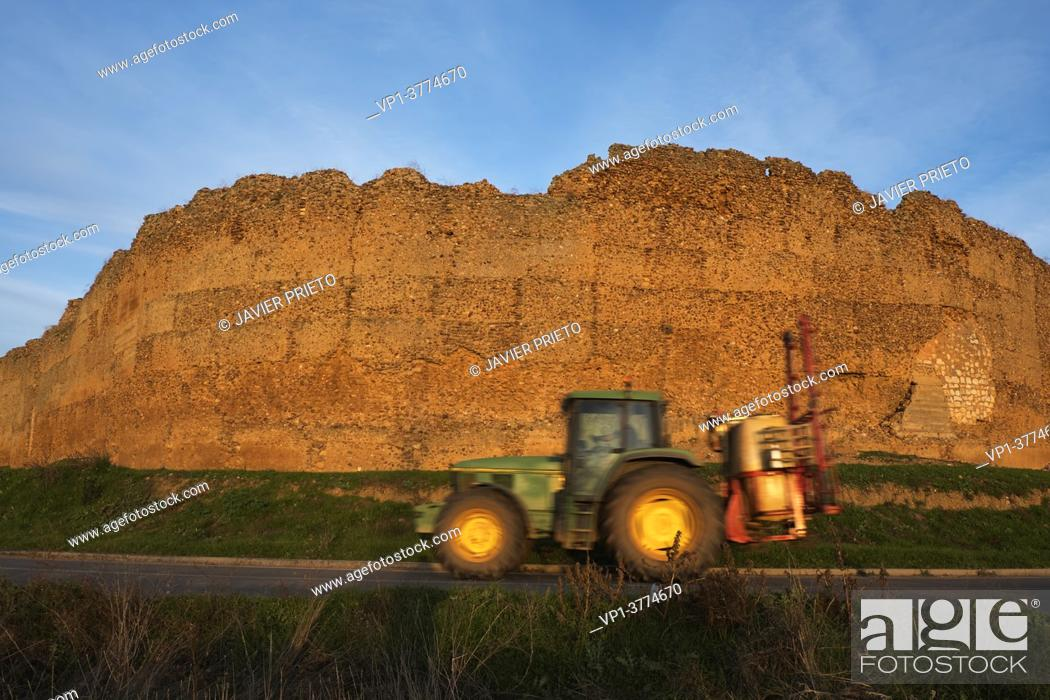 Stock Photo: At sunset, a tractor passes by the walls of the old castle of San Pedro de Latarce, on the Camino de Santiago del Sureste as it passes through the province of.