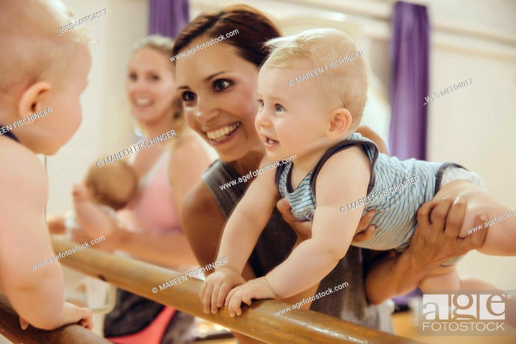 Stock Photo: Mother holding up her baby to barre in dance studio.