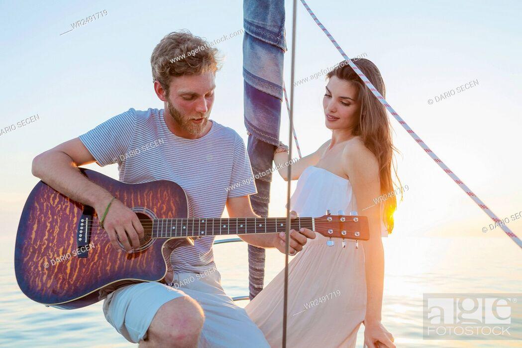 Stock Photo: Young man playing guitar on sailboat.