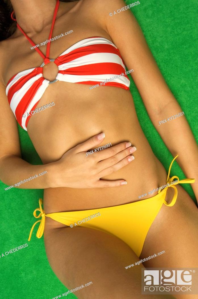 Stock Photo: Mid section view of a woman sunbathing.