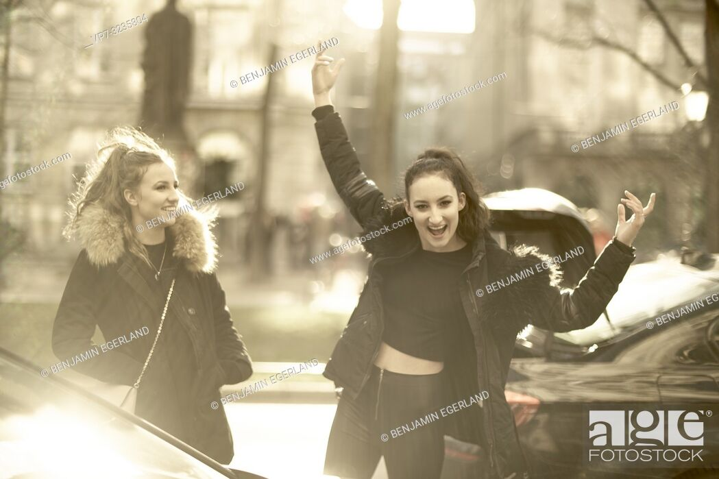Photo de stock: Two young vibrant sisters at street in city, wearing winter clothing, Munich, Germany.