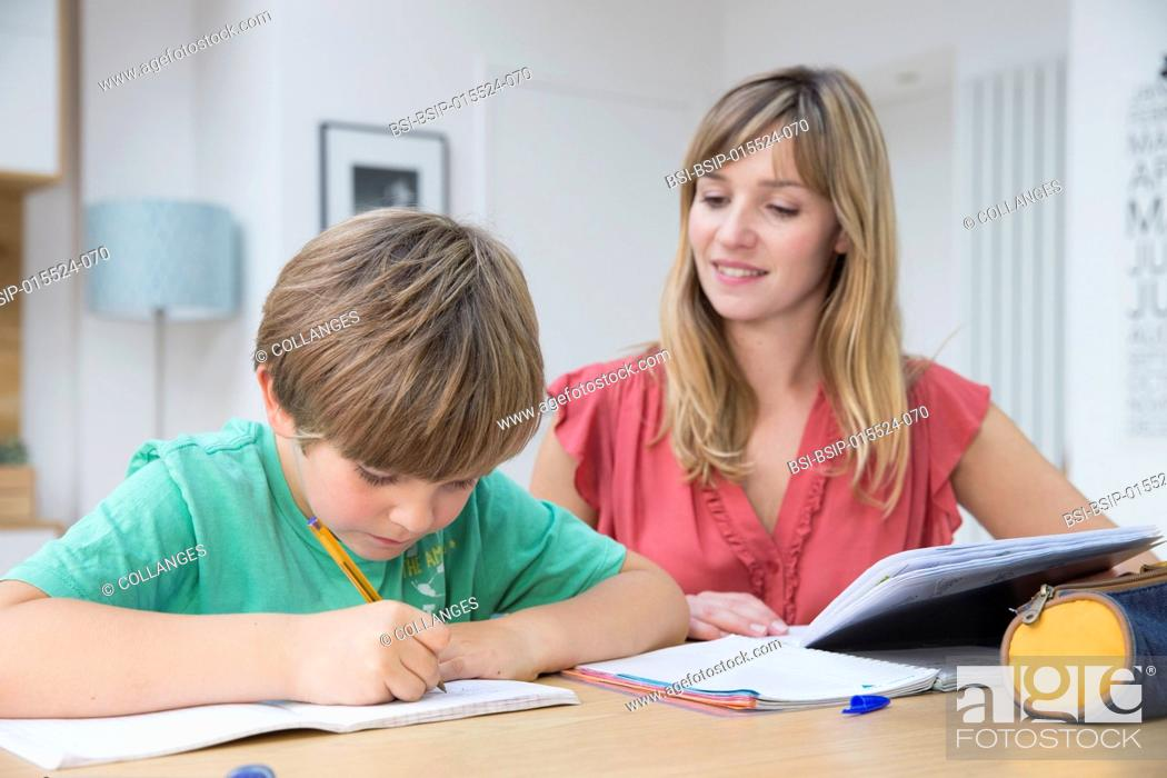 Stock Photo: A child doing homework with his mother.