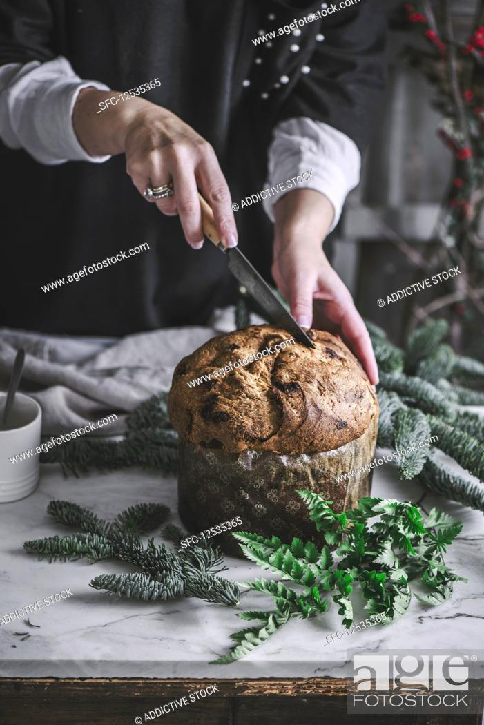 Imagen: Crop person cutting fresh baked tasty Panettone on kitchen table.
