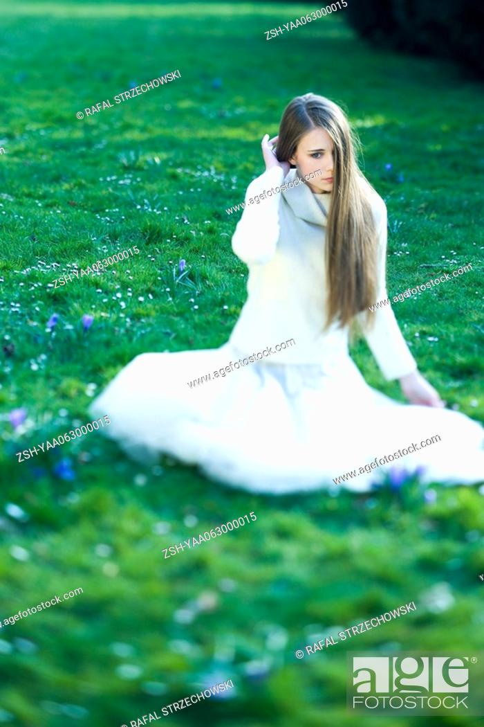 Stock Photo: Teenage girl sitting in grass, hair partially covering face, looking away.
