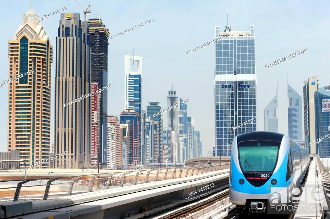 Stock Photo: View of Dubai metro train and office towers in financial district of Dubai United Arab Emirates UAE.