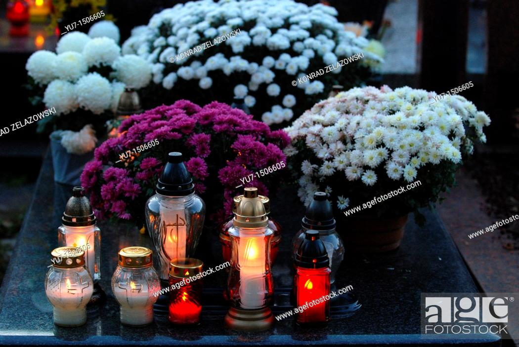 Stock Photo: Chrysanthemums and candles on Wolski cemetery in Warsaw, Poland during All Saints Day.