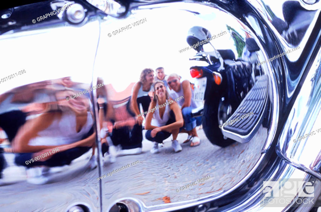 Stock Photo: Reflection of a group of friends on a chrome surface.