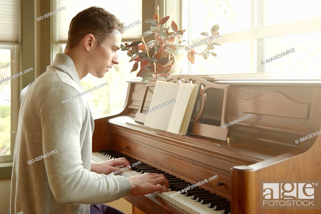 Stock Photo: Young man playing the piano in living room.