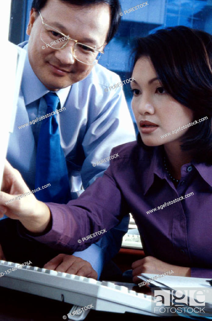 Stock Photo: Businessman and a businesswoman sitting in front of a computer.
