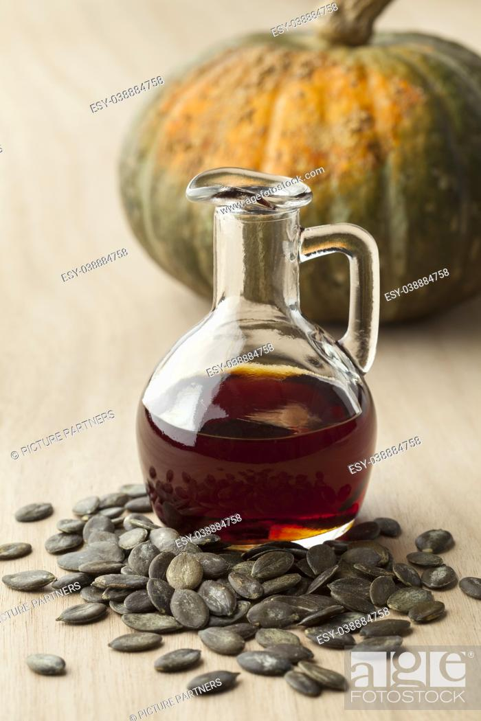 Stock Photo: Bottle with tasty pumpkin seed oil and roasted seeds.