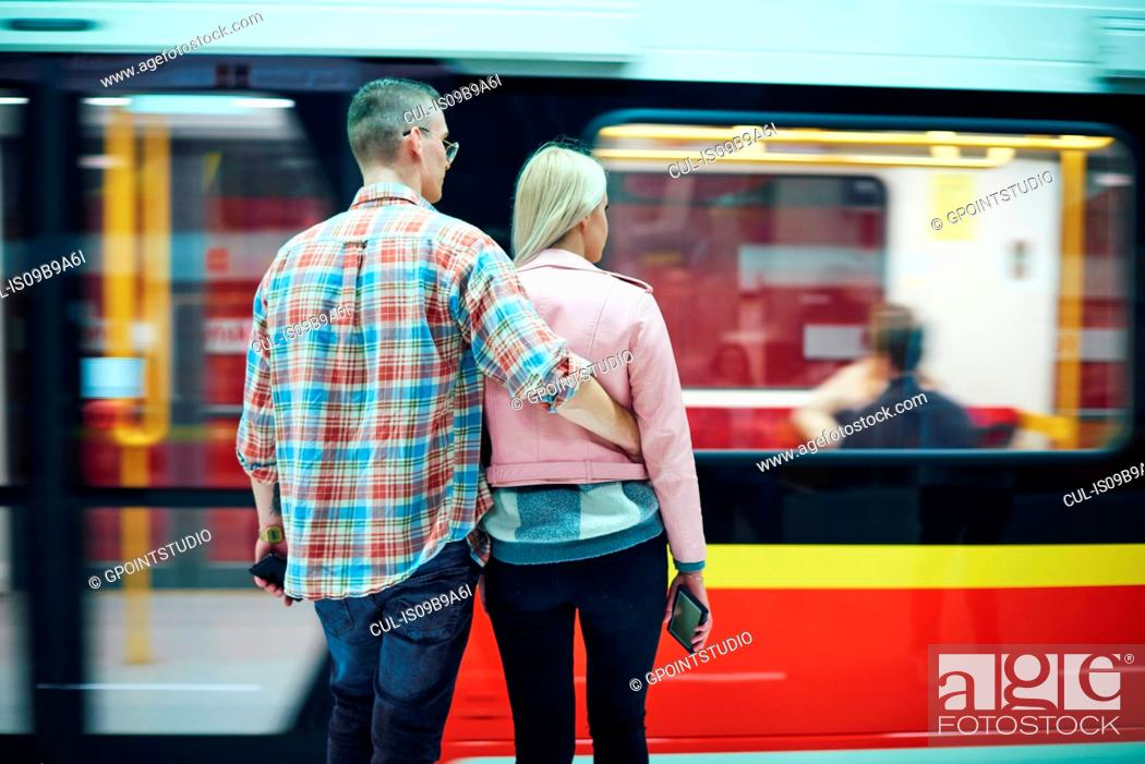 Stock Photo: Rear view of young couple waiting at city tram station.