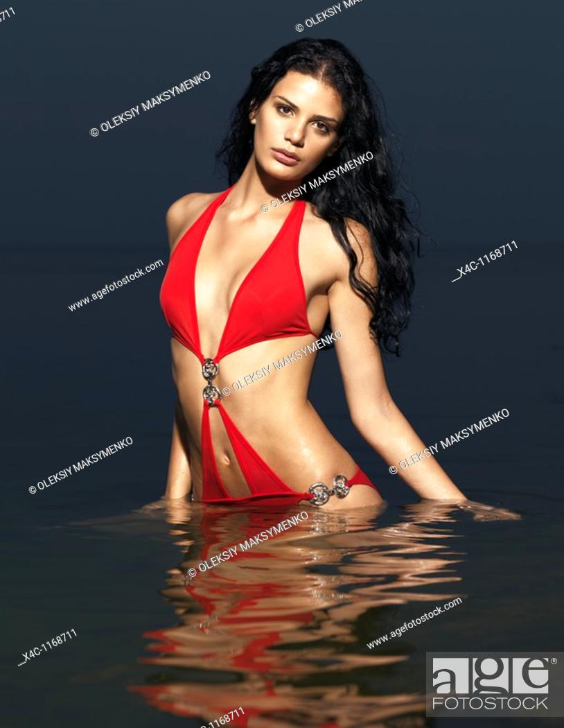 Stock Photo: Beautiful young woman in red swim suit standing in water  High fashion photo.