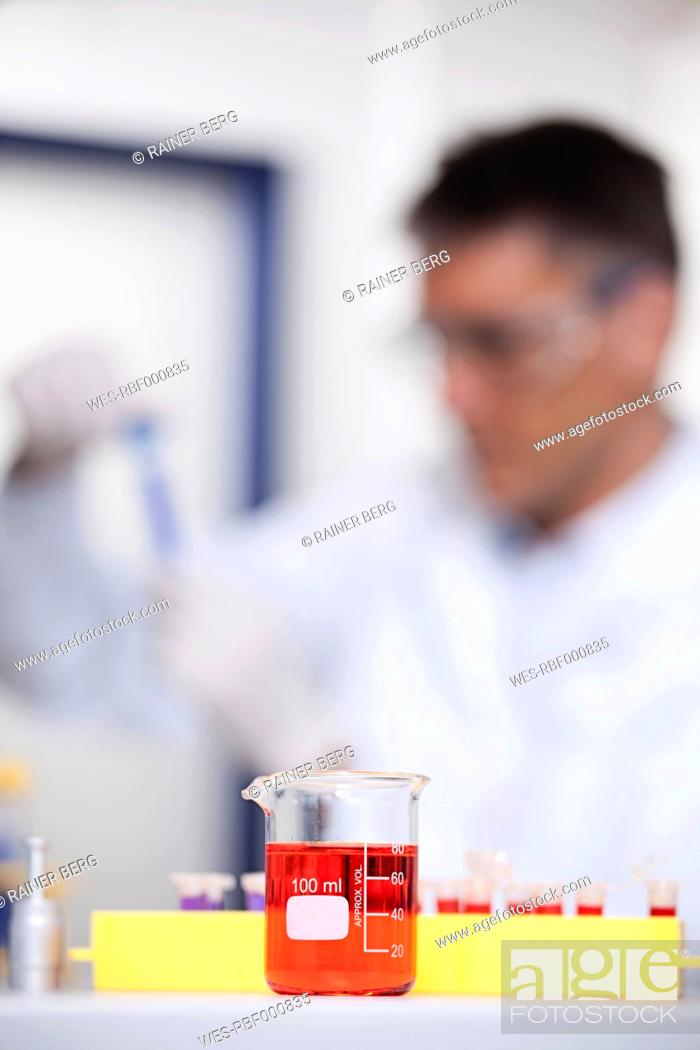 Stock Photo: Germany, Bavaria, Munich, Red liquid in beaker, scientist doing medical research in background.