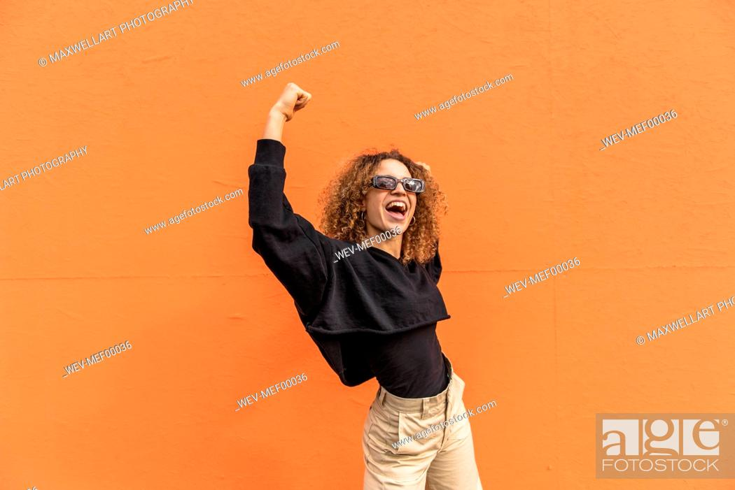 Imagen: Cheerful woman with arms raised standing against orange wall.