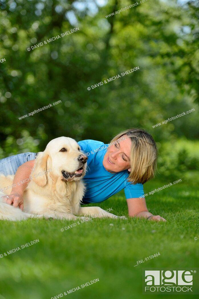 Stock Photo: Mature woman with a golden retriever in garden.
