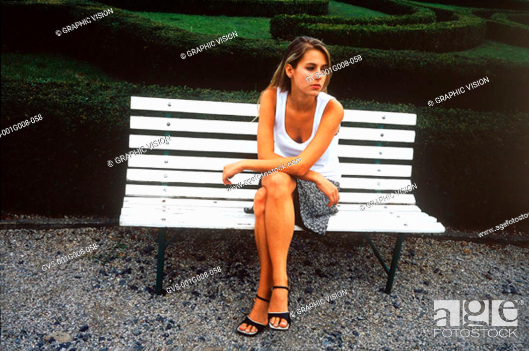 Stock Photo: Young woman sitting on a park bench.