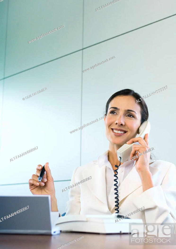 Stock Photo: Businesswoman using landline phone.