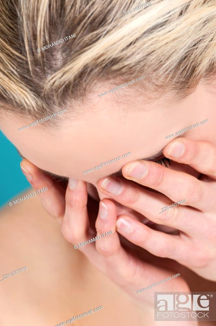 Stock Photo: Young Caucasian woman hiding face with hands.