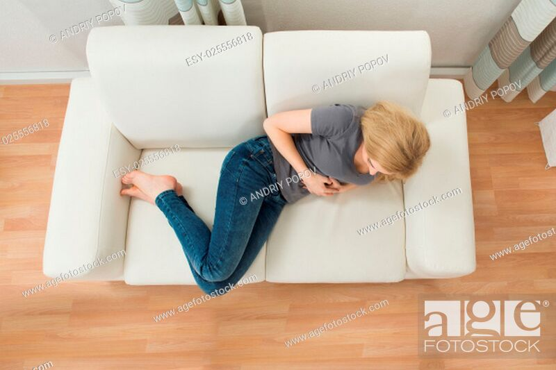 Stock Photo: Young Woman On Sofa Suffering From Stomachache.