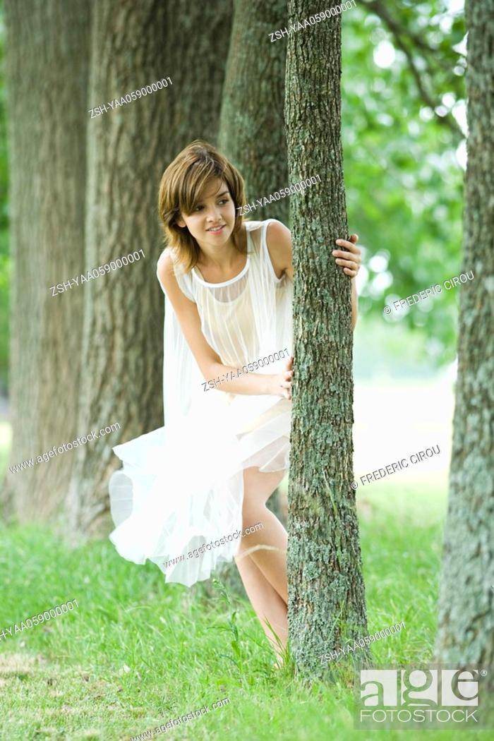 Stock Photo: Young woman wearing dress, peeking around tree.