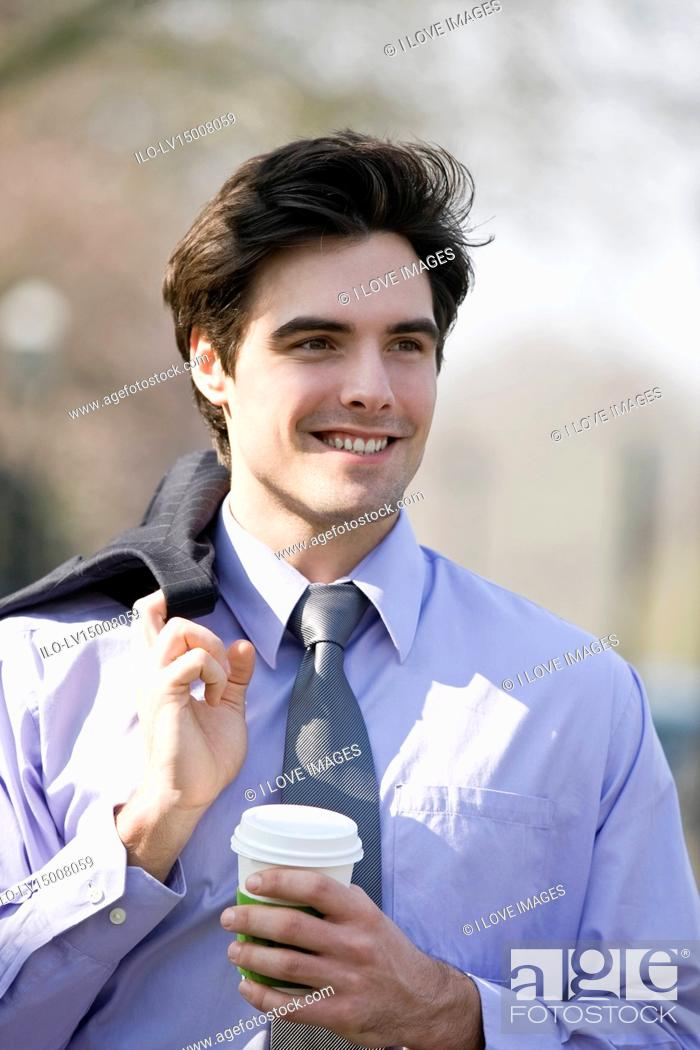 Stock Photo: A businessman walking, holding a hot drink.