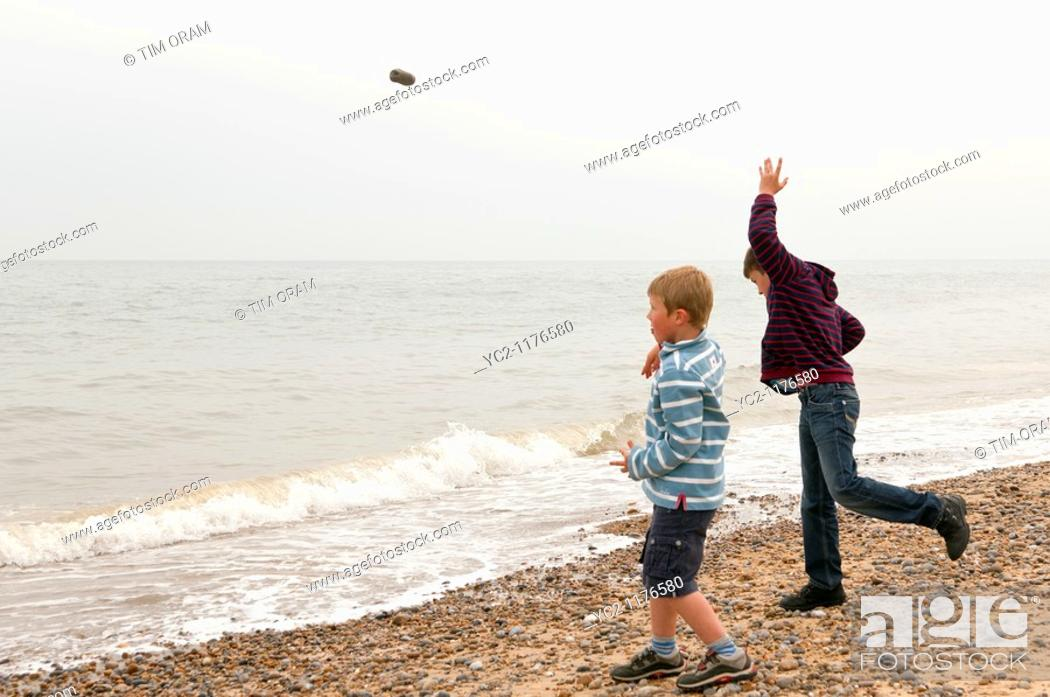 Stock Photo: two boys 6 & 10 throwing stones into the sea on a UK beach.