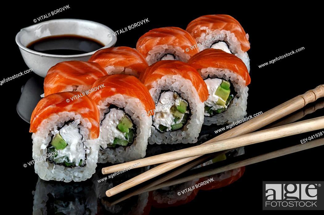 Stock Photo: Philadelphia sushi rolls with chopsticks and soy sauce. Black background. Reflection.