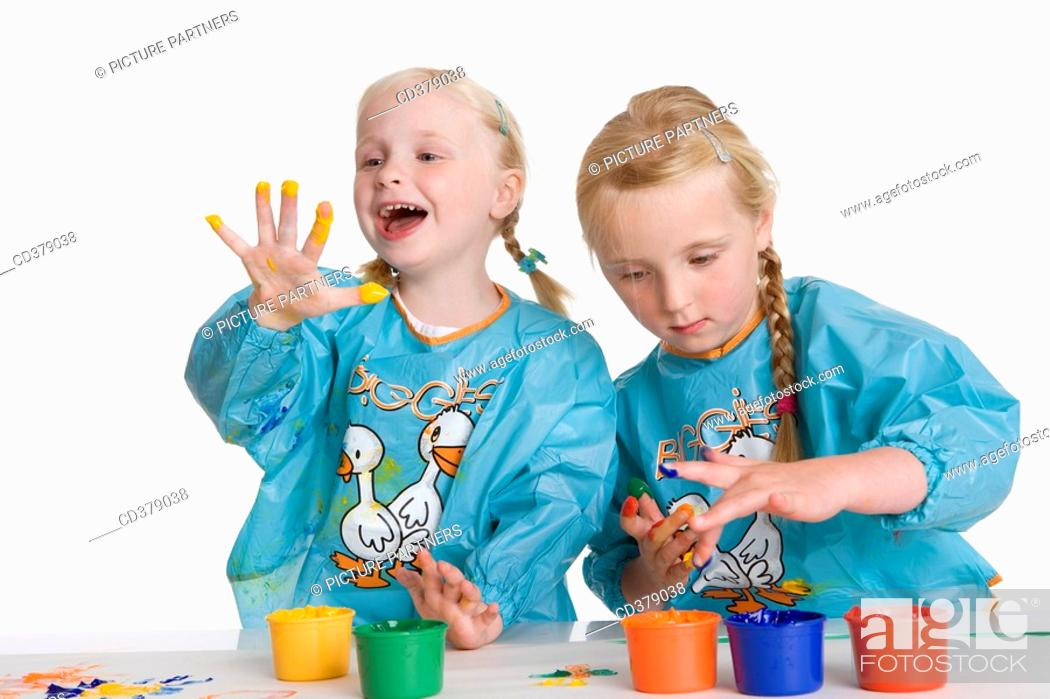 Stock Photo: Two blond girls fingerpainting.