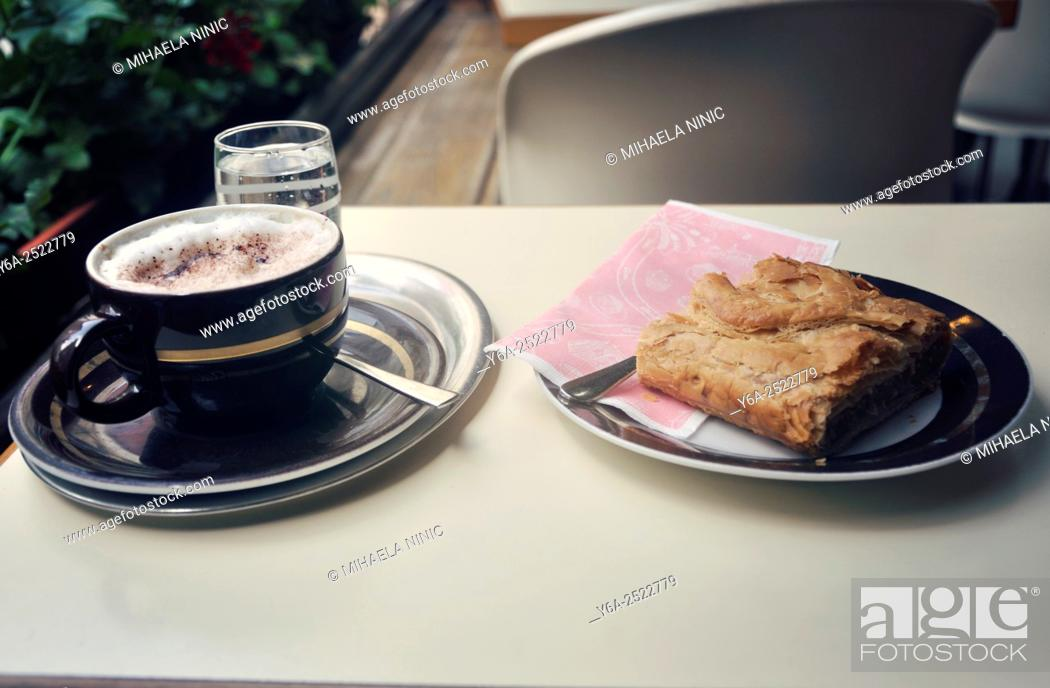 Stock Photo: Glass of water, teaspoon, coffee cup on a plate and Apple strudel, close up, Vienna, Austria.
