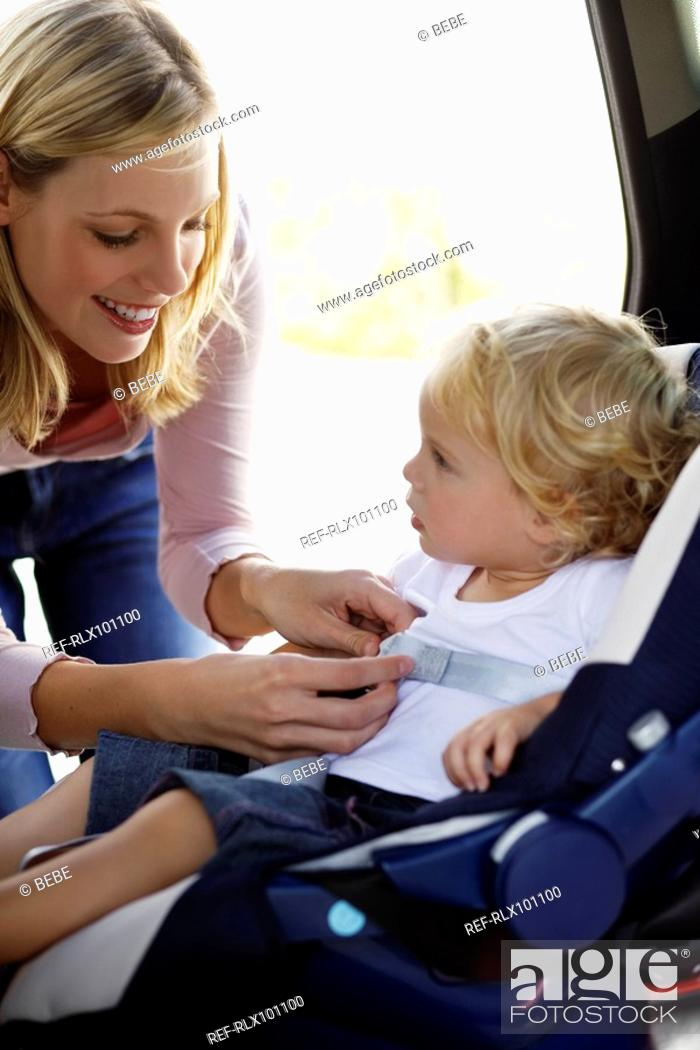 Stock Photo: Young mother securing baby 12-24 months in car seat.