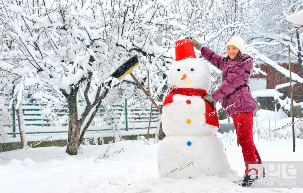 Stock Photo: snowman and young girl.