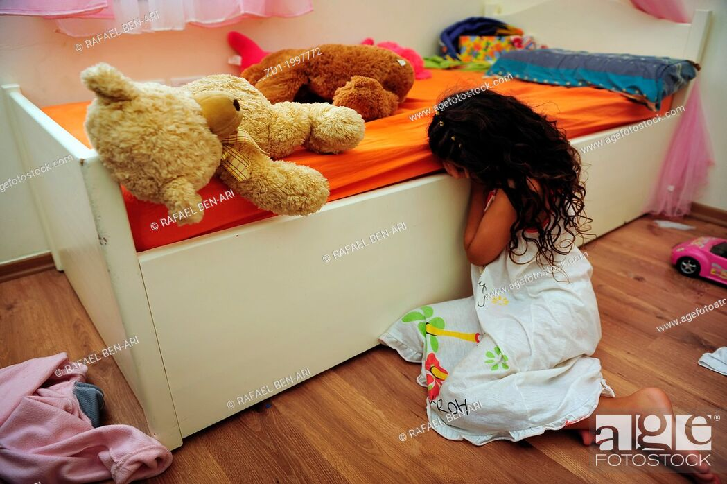 Stock Photo: A young girl who is a victim of domestic violence cries on the floor of her bedroom.