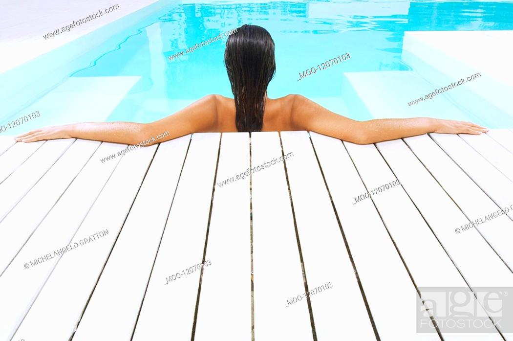 Stock Photo: Young Woman in Swimming Pool resting on poolside back view.