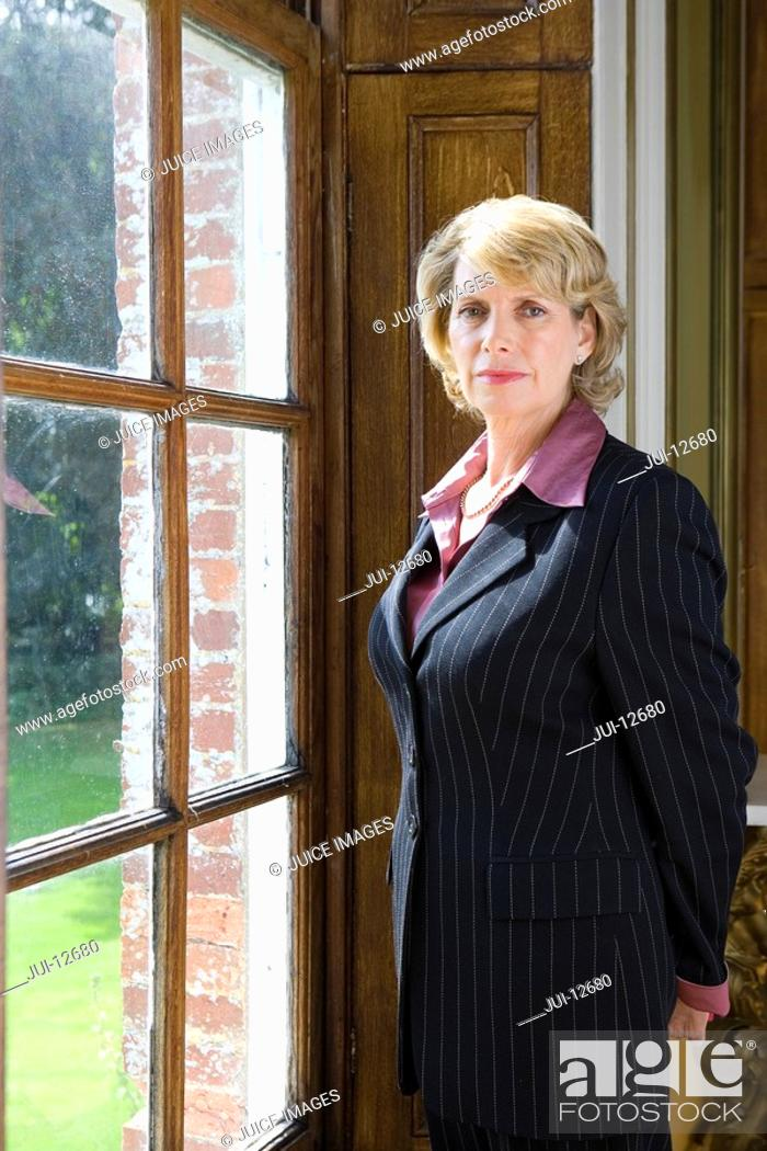 Stock Photo: Mature businesswoman looking out window, portrait.