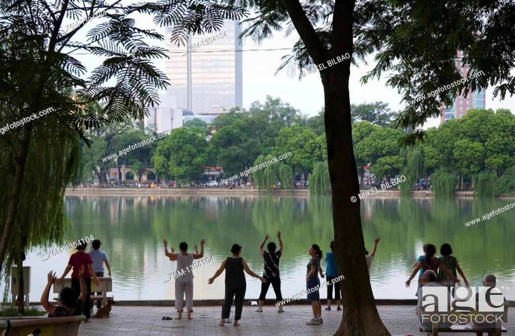 Stock Photo: People doing exercise by Hoan Kiem lake. Hanoi, Vietnam.