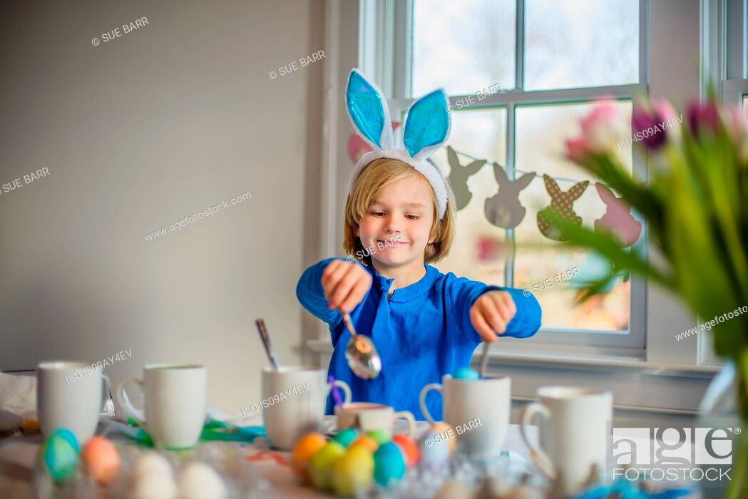 Stock Photo: Boy at table wearing bunny ears decorating eggs for Easter.