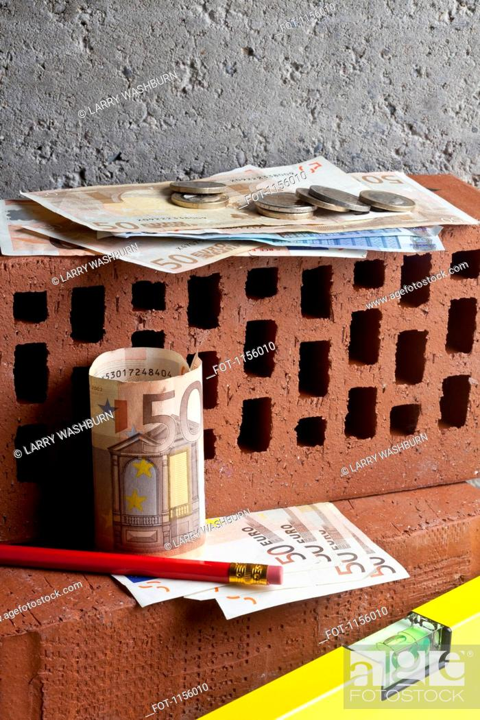Stock Photo: A pile of money on stacked bricks with a pencil and level.