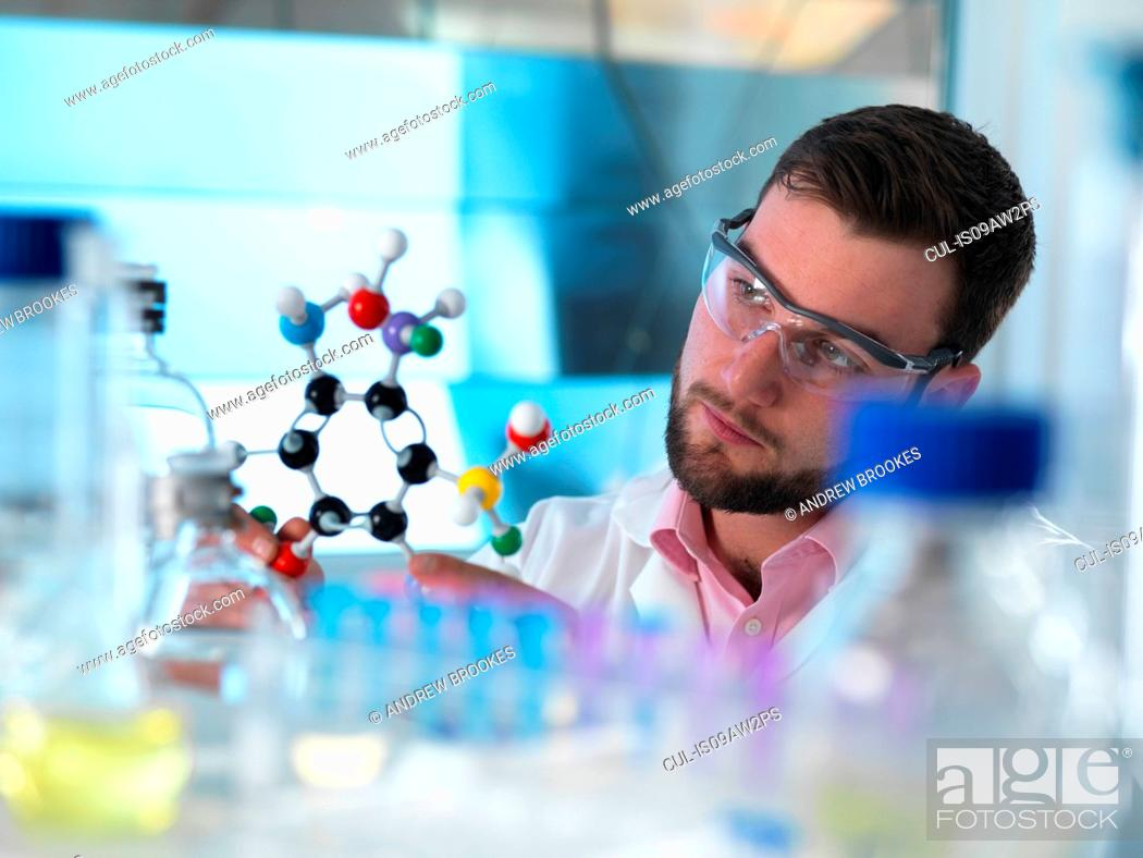 Stock Photo: Scientist examining molecular model in laboratory.