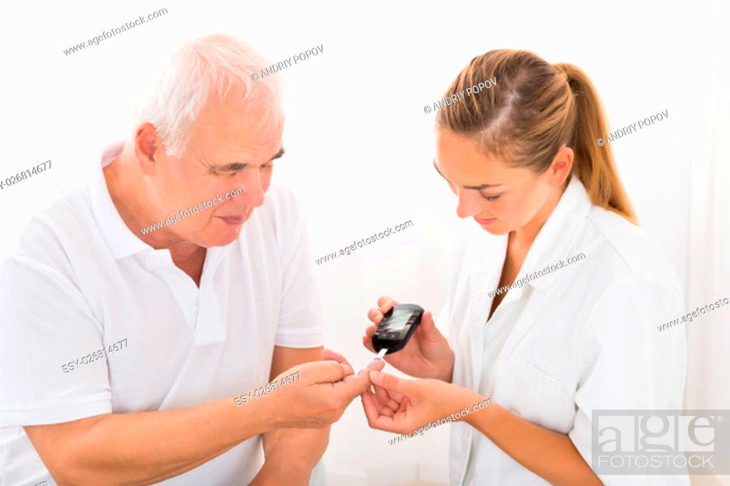 Stock Photo: Young Female Doctor Using Glucometer On Senior Male Patient's Finger.
