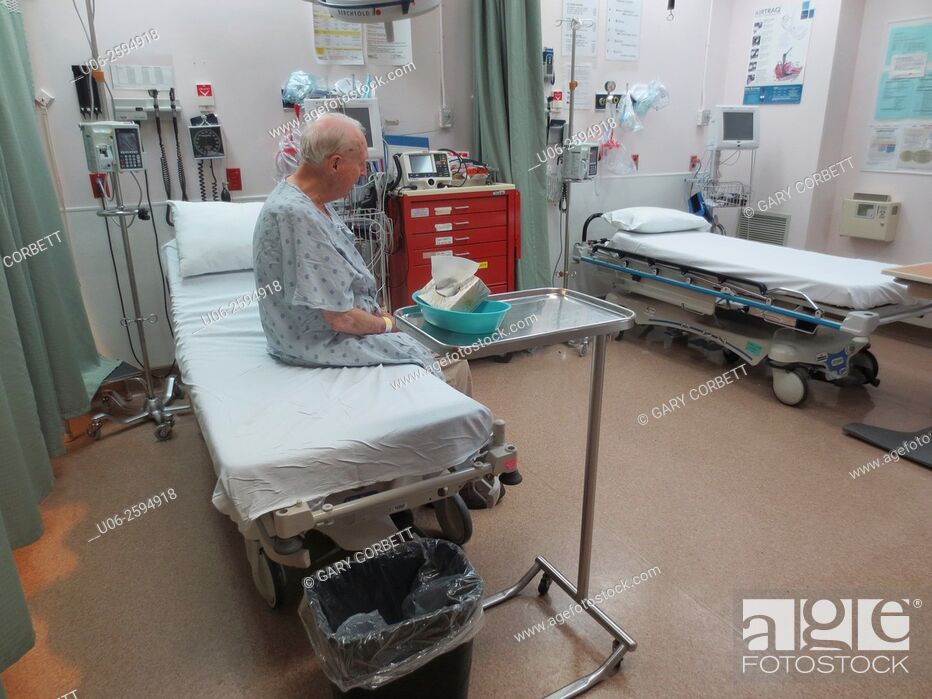 Stock Photo: A senior man sitting on an examination bed in emergency at a hospital waiting for a doctor.