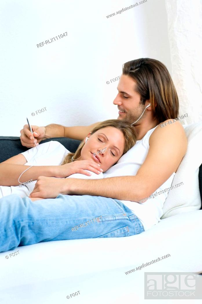 Stock Photo: Young couple listening to MP3 player.