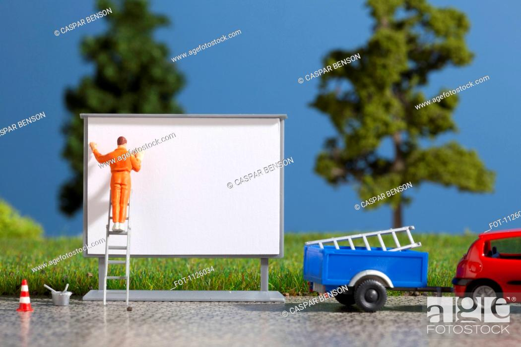 Stock Photo: A diorama of a miniature worker billboard posting.