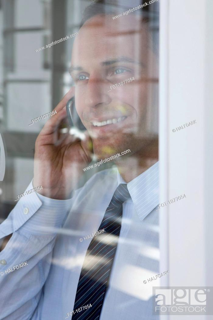Stock Photo: A businessman talking on a mobile phone, viewed through window.
