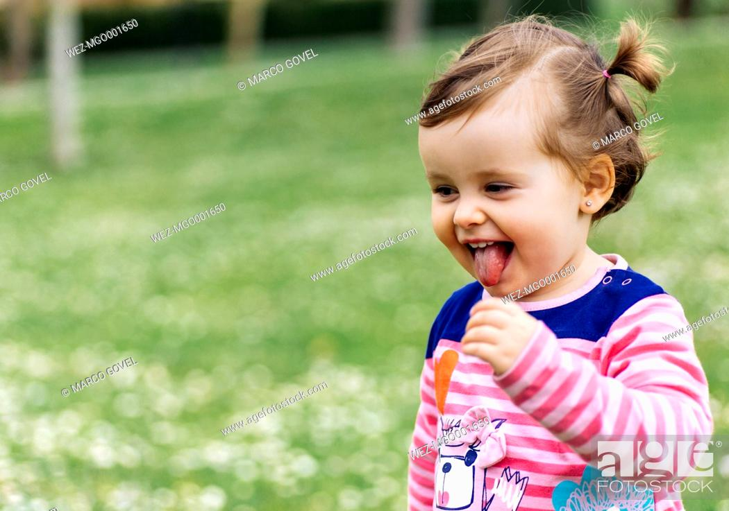 Imagen: Little girl with braids sticking out tongue.