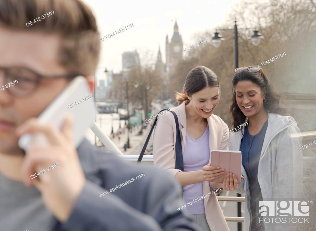 Stock Photo: Female friends using digital tablet on urban bridge, London, UK.