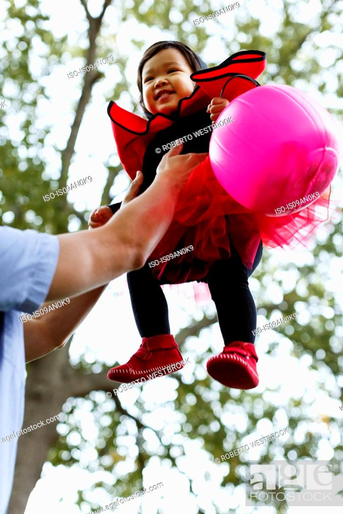 Stock Photo: Father lifting daughter into the air.