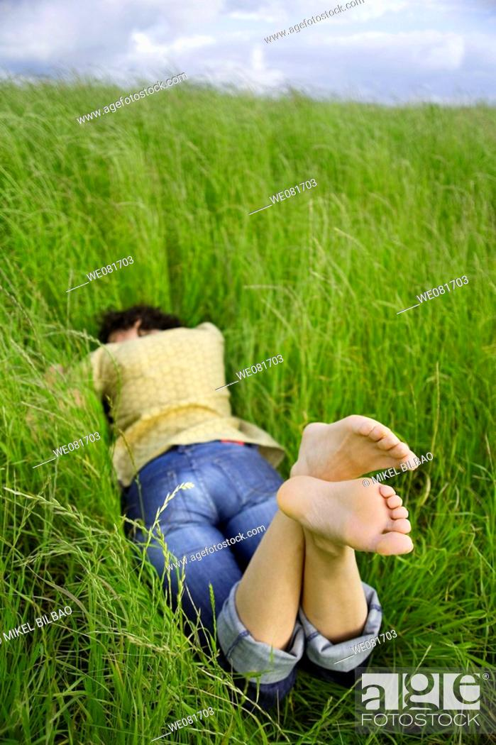 Stock Photo: Young barefooted woman resting on a peaceful field of grass.