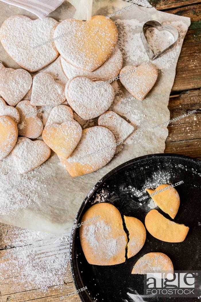 Stock Photo: Heart-shaped shortbreads sprinkled with icing sugar on parchment paper and baking pan.