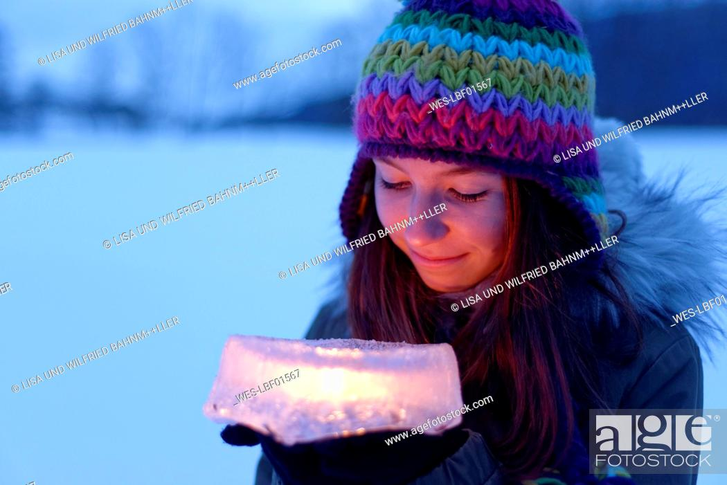 Stock Photo: Smiling teenage girl holding cake made of ice with candle inside.